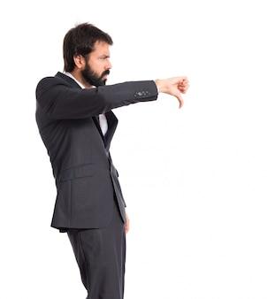 Бизнесмен делает плохой сигнал на белом фоне