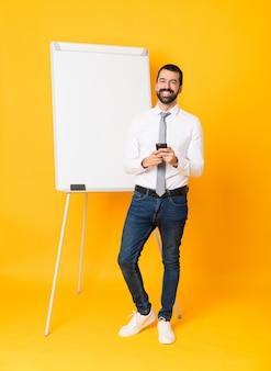 携帯電話でメッセージを送信する分離された黄色の上にホワイトボードでプレゼンテーションを行う実業家の全身ショット