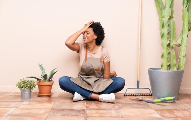 植物の間で床に座って庭師女性
