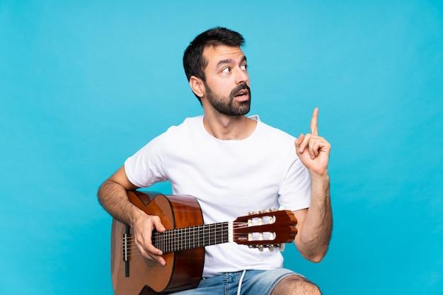 指を上向きのアイデアを考えて分離上のギターを持つ若い男