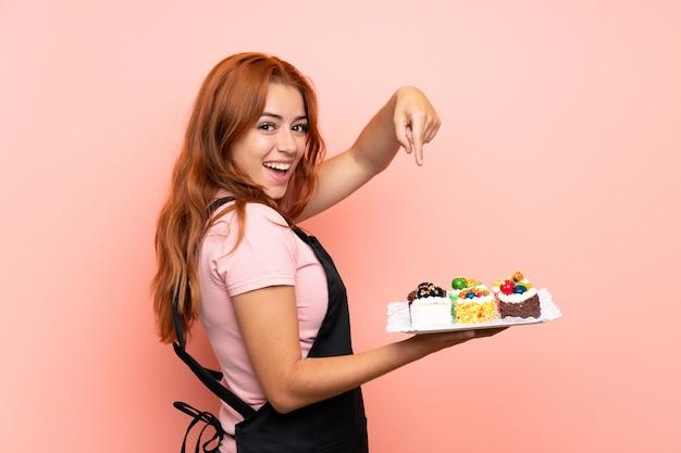 ティーンエイジャーの赤毛の女の子がたくさんの異なるミニケーキを分離し、それを指して