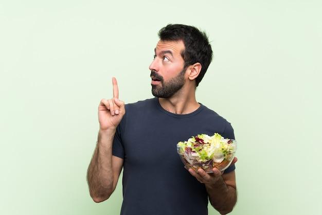 指を上向きのアイデアを考えて孤立した緑の壁の上のサラダと若いハンサムな男