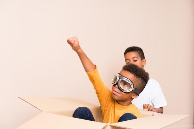 Афро-американские братья играют. мальчик внутри картонной коробки с авиатор очки