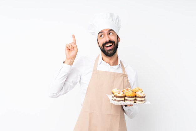若い男が指を持ち上げながら解決策を実現するために分離を意図してマフィンケーキをかざす