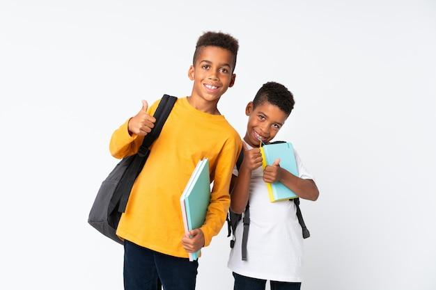 Два мальчика афро-американских студентов над изолированы и с большим пальцем вверх