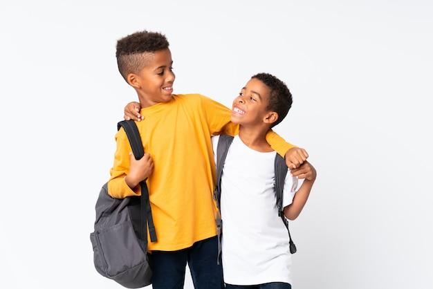 Счастливые два мальчика афро-американских студентов над изолированными