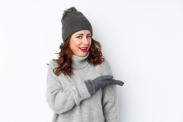 来て招待するための側に分離された拡張手を介して冬の帽子を持つ若いロシア人女性