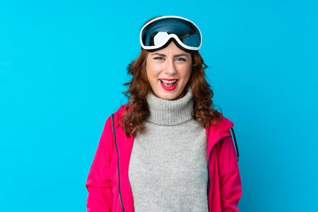 驚きの表情で孤立した青い壁の上のスノーボードメガネのスキーヤー女性