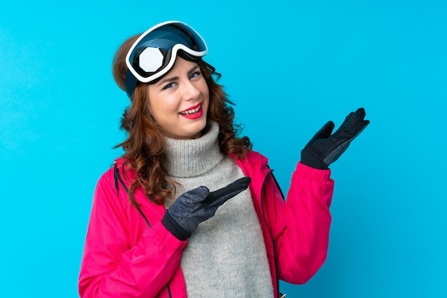 来て招待する側に手を伸ばす分離の青い壁の上のスノーボードメガネのスキーヤーの女性