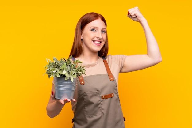 Рыжий молодой садовник женщина держит растение над желтой стене, празднующей победу