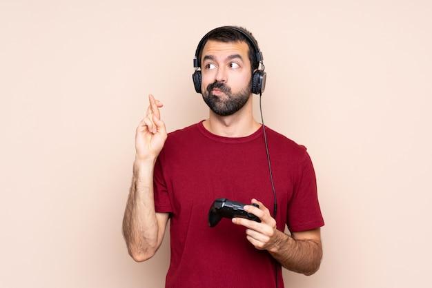 指を交差し、最高を願って孤立した壁を越えてビデオゲームコントローラーで遊ぶ男