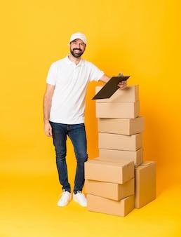 孤立した黄色の壁の上のボックスの中で配達人の全身ショット