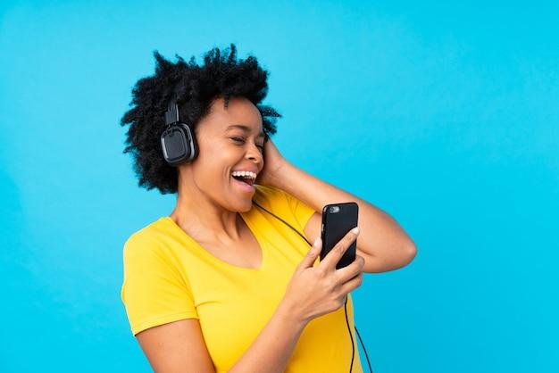 携帯電話で音楽を聴く若いアフリカ系アメリカ人女性