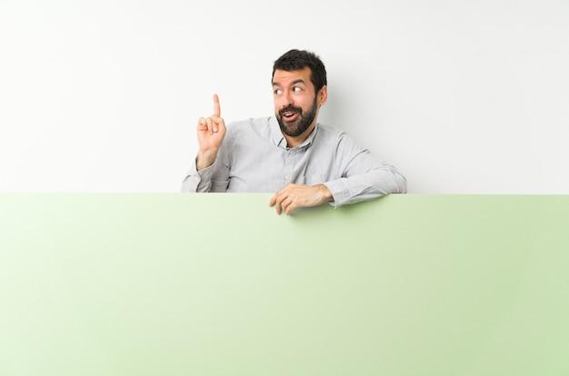 指を持ち上げながら解決策を実現するつもりの大きな緑の空のプラカードを保持しているひげの若いハンサムな男