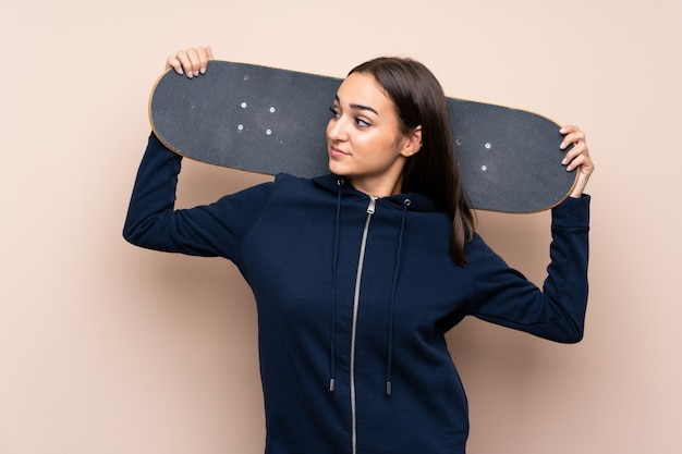 Молодая женщина на изолированном фоне с кататься на коньках и глядя в сторону