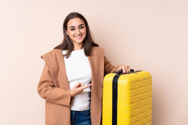Путешественник женщина с чемоданом и указывая его
