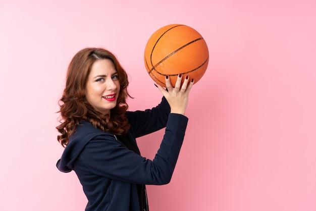バスケットボールのボールで孤立したピンクの背景の上の若いロシア人女性