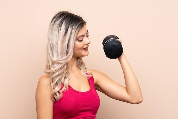 重量挙げを作る分離の背景の上のティーンエイジャーのスポーツ少女