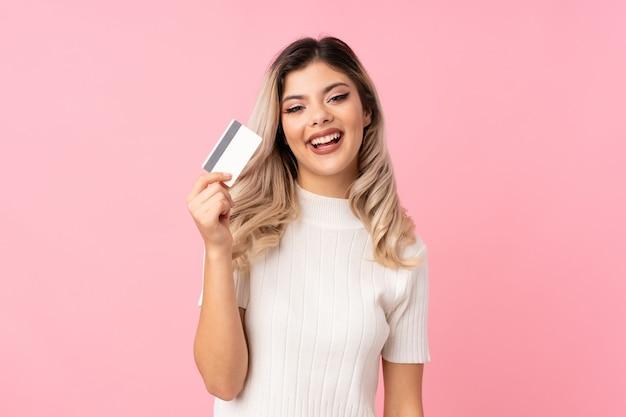 クレジットカードを保持している分離のピンクの背景の上のティーンエイジャーの女の子