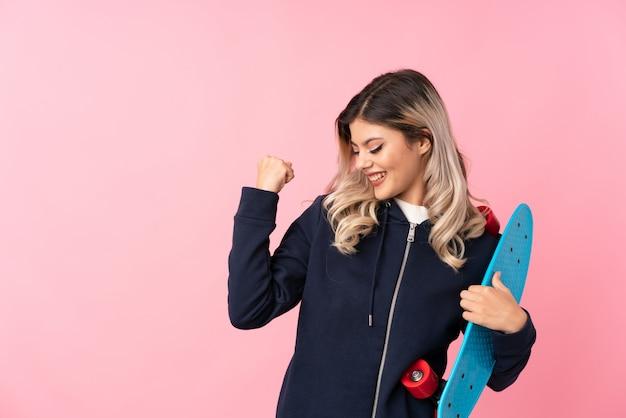 スケートと勝利のジェスチャーを作ると分離のピンクの背景の上のティーンエイジャーの女の子