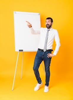 離れて指している孤立した黄色の背景の上にホワイトボードでプレゼンテーションを行う実業家の全身ショット