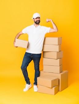 強いジェスチャーをしている孤立した黄色の背景上のボックスの中で配達人の全身ショット
