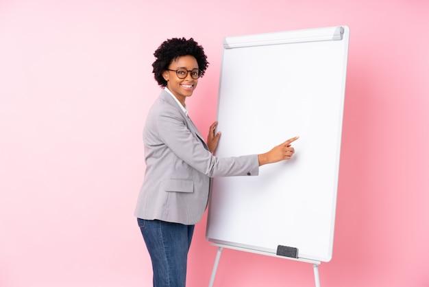 孤立したピンクの背景上のホワイトボードとブルネットの実業家
