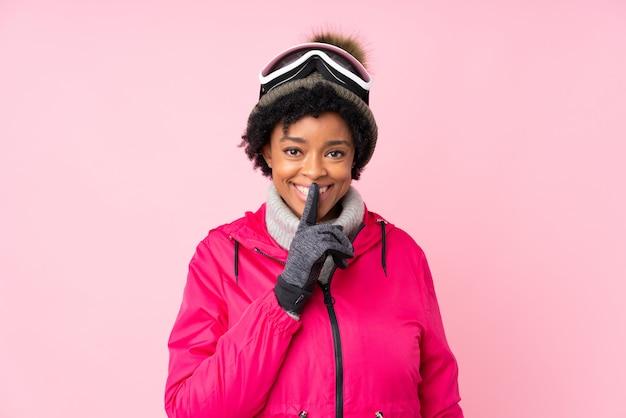 孤立したピンクの背景の上の雪のメガネでブルネットの女性