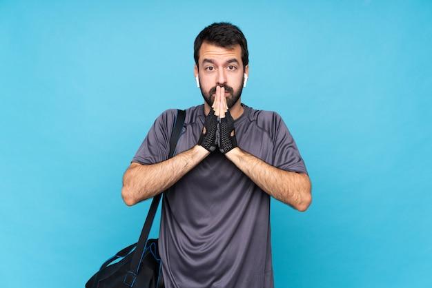 Молодой спортивный человек с бородой держит ладонь вместе