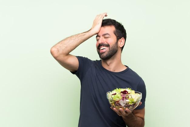 サラダを持つ若いハンサムな男は何かを実現し、解決策を意図しています