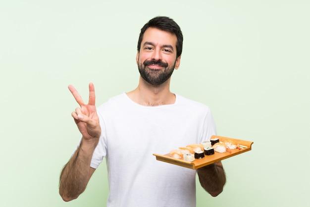 Молодой красавец с суши, показывая знак победы обеими руками