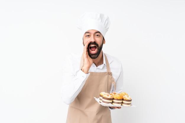 Молодой человек, держащий кекс торт, крича и объявив что-то