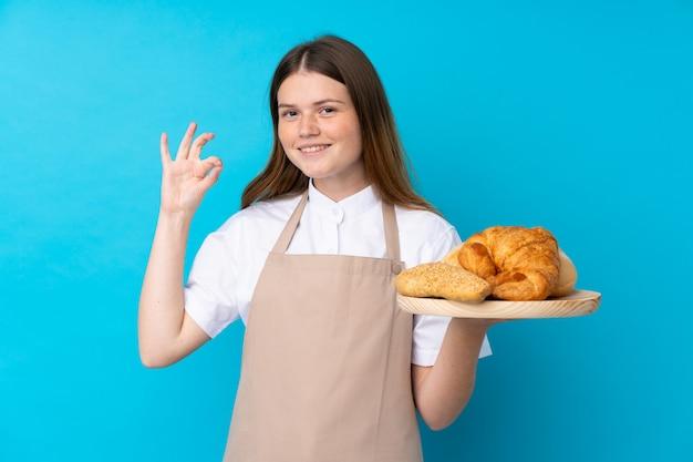Женский пекарь держит стол с несколькими хлебов, показывая знак ок с пальцами