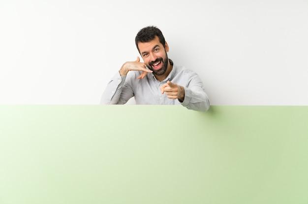 電話のジェスチャーを作ると指している大きな緑の空のプラカードを保持しているひげの若いハンサムな男