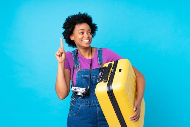 孤立した青い背景にスーツケースを保持しているブルネットの女性