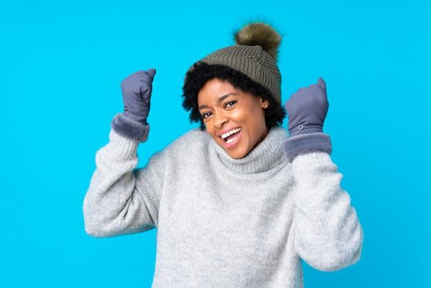 Брюнетка в зимней шапке на синем фоне