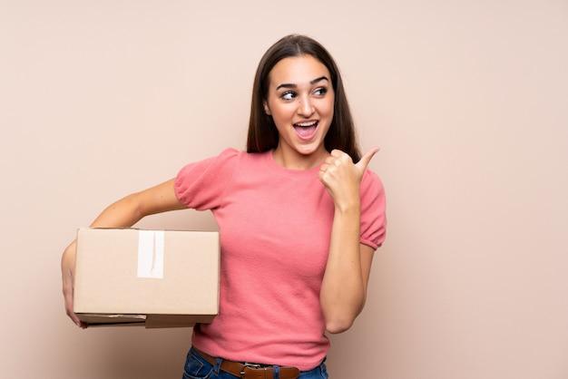 Молодая женщина держит коробку, чтобы переместить ее на другой сайт и указывая сторону