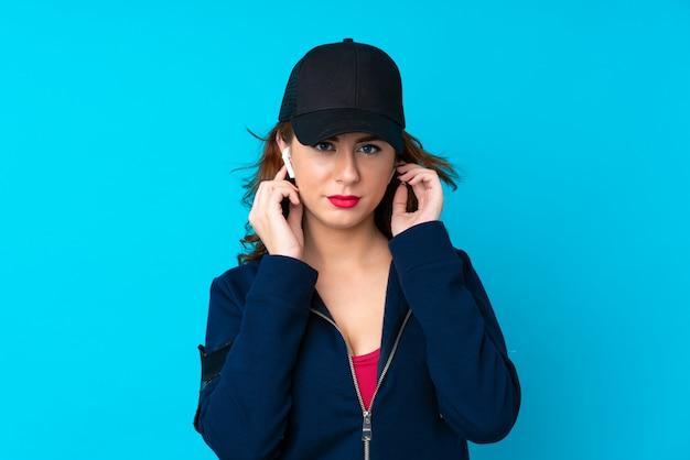 Молодая женщина спортивного прослушивания музыки и глядя на фронт