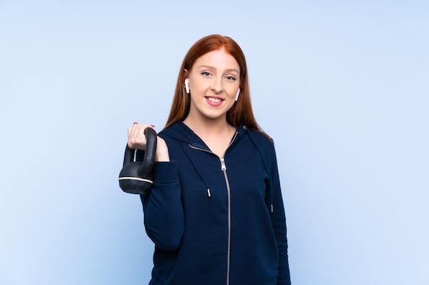 Молодая рыжая спортивная женщина делает тяжелую атлетику с гирей