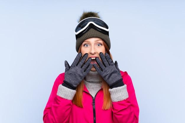 驚きの表情でスノーボードメガネのスキーヤー赤毛の女性