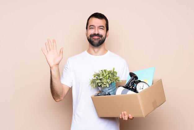 箱を持って、幸せな表情で手で敬礼する新しい家に移動する男