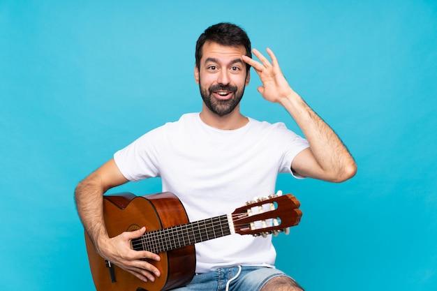 孤立した青い壁の上のギターを持つ若い男はちょうど何かを実現し、解決策を意図しています