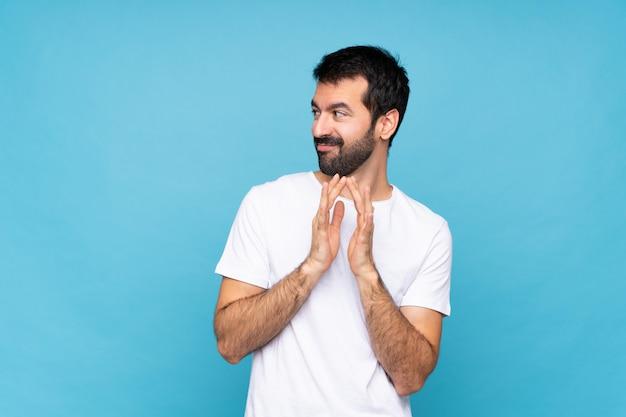 何かをスキーム分離の青い壁の上のひげと若い男
