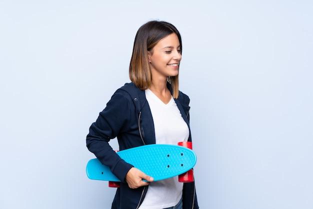 スケートで孤立した青い壁の上の若い女性