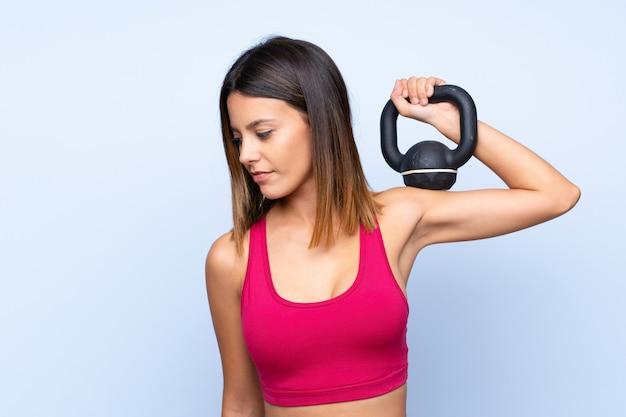 Молодая женщина спорта над изолированной голубой стеной делая поднятие тяжестей с гирей