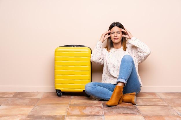 不満と何かに不満の床に座ってスーツケースを持つ旅行者の女性。負の表情
