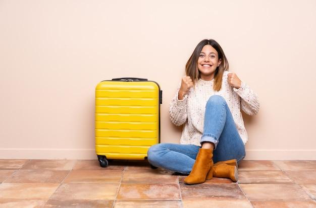 Путешественник женщина с чемоданом, сидя на полу, празднует победу