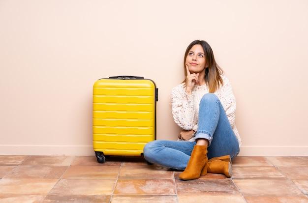 Путешественник женщина с чемоданом, сидя на полу, думая, идея