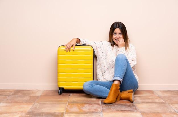 Путешественница с чемоданом сидит на полу, нервная и напуганная