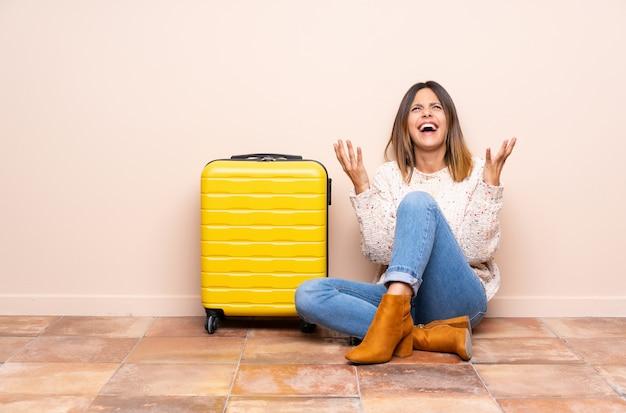 不満と何かに不満の床に座ってスーツケースを持つ旅行者女性